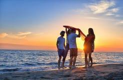 Gruppo di giovani felici che ballano alla spiaggia sul bello tramonto di estate Immagini Stock Libere da Diritti