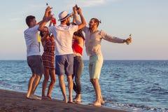 Gruppo di giovani felici che ballano alla spiaggia sul bello tramonto di estate Immagine Stock Libera da Diritti