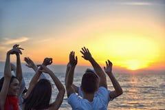 Gruppo di giovani felici che ballano alla spiaggia sul bello tramonto di estate Fotografie Stock Libere da Diritti