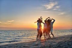 Gruppo di giovani felici che ballano alla spiaggia sul bello tramonto di estate Fotografia Stock