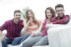 Gruppo di giovani felici che si siedono sullo strato Fotografia Stock