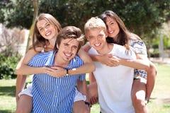 Gruppo di giovani felici che trasportano sulle spalle Fotografia Stock