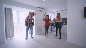 Gruppo di giovani felici e di donne che eseguono a due vie in appartamento al rallentatore