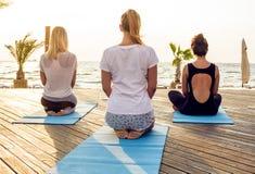 Gruppo di giovani femmine che praticano yoga sulla spiaggia durante l'alba fotografia stock libera da diritti