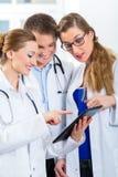 Gruppo di giovani medici in clinica con il computer della compressa Immagine Stock