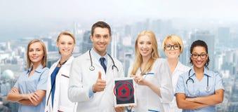 Gruppo di giovani medici con il computer del pc della compressa Fotografia Stock