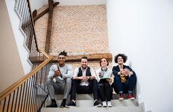 Gruppo di giovani persone di affari che si siedono sulle scale all'interno, esaminante macchina fotografica immagine stock libera da diritti