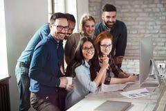 Gruppo di giovani progettisti che lavorano come gruppo Immagine Stock