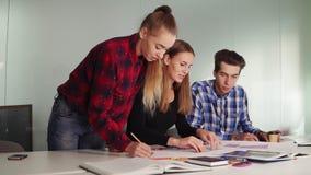 Gruppo di giovani progettisti freschi dei pantaloni a vita bassa nell'abbigliamento casual che lavora insieme nella sala riunioni video d archivio