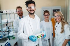 Gruppo di giovani riusciti scienziati che posano per la macchina fotografica Fotografia Stock