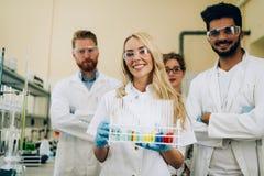 Gruppo di giovani riusciti scienziati che posano per la macchina fotografica Immagini Stock