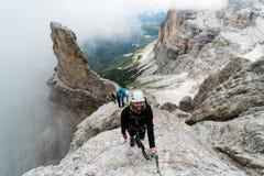 Gruppo di giovani scalatori di montagna su un ripido via Ferrata con una vista imponente delle dolomia italiane fotografie stock libere da diritti