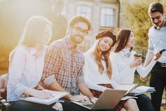 Gruppo di giovani siedasi freelance hipster fotografie stock