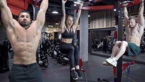 Gruppo di giovani di sport che fanno gli esercizi del muscolo addominale facendo uso di una barra orizzontale nella palestra archivi video