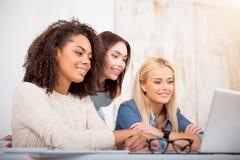 Gruppo di giovani studentesse che per mezzo di un computer portatile Fotografie Stock