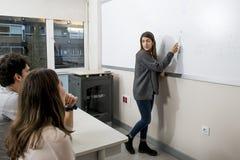 Gruppo di giovani studenti che prendono lezione all'aula dell'università con la ragazza che stanno sulla spiegazione della lavagn Fotografie Stock