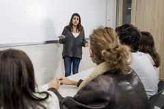 Gruppo di giovani studenti che prendono lezione all'aula dell'università con la ragazza che stanno sulla spiegazione della lavagn Fotografia Stock
