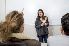 Gruppo di giovani studenti che prendono lezione all'aula dell'università con la ragazza che stanno sulla spiegazione della lavagn Immagini Stock Libere da Diritti