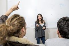 Gruppo di giovani studenti che prendono lezione all'aula dell'università con la ragazza che stanno sulla spiegazione della lavagn Fotografia Stock Libera da Diritti