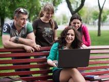 Gruppo di giovani studenti di college che per mezzo del computer portatile Fotografia Stock Libera da Diritti