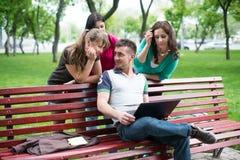 Gruppo di giovani studenti di college che per mezzo del computer portatile Immagine Stock Libera da Diritti