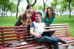 Gruppo di giovani studenti di college che per mezzo del computer portatile Fotografia Stock