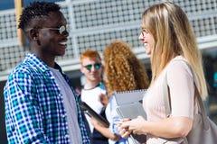 Gruppo di giovani studenti felici che parlano in un'università Immagine Stock Libera da Diritti