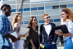 Gruppo di giovani studenti felici che parlano in un'università Fotografie Stock Libere da Diritti
