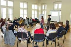 Gruppo di giovani studenti universitari che hanno una discussione di gruppo che si siede insieme su un cerchio delle sedie e di c fotografia stock