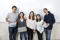 Gruppo di giovani studenti universitari teenager che posano insieme stare Immagine Stock