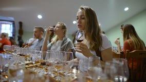 Gruppo di giovani su un assaggio di vino Ragazza con un bicchiere di vino, assaggia il gusto e l'odore della bevanda stock footage