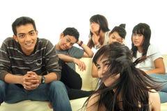 Gruppo di giovani sul sofà Immagine Stock