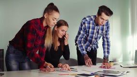 Gruppo di giovani sulla riunione in appartamento moderno Tre studenti che lavorano al loro compito che si siede insieme a stock footage