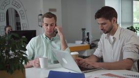 Gruppo di giovani uomini d'affari che lavorano all'ufficio di mattina archivi video