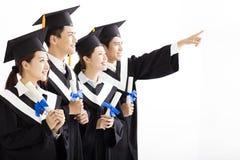 Gruppo di graduazione che guarda e che indica il futuro Immagini Stock