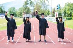 Gruppo di graduazione di studenti che celebrano sulla pista atletica con Fotografie Stock Libere da Diritti