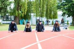 Gruppo di graduazione di studenti che celebrano sulla pista atletica, preparazione Immagine Stock Libera da Diritti