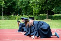 Gruppo di graduazione di studenti che celebrano sulla pista atletica, preparazione Immagini Stock Libere da Diritti