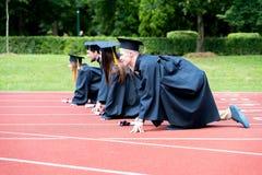 Gruppo di graduazione di studenti che celebrano sulla pista atletica, preparazione Fotografie Stock Libere da Diritti