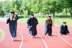 Gruppo di graduazione di studenti che celebrano sulla pista atletica, preparazione Fotografia Stock