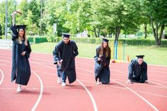 Gruppo di graduazione di studenti che celebrano sulla pista atletica, preparazione Immagine Stock