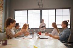 Gruppo di imprenditori attraenti nella riunione con le finestre luminose e la tavola di conferenza stipata di Immagini Stock