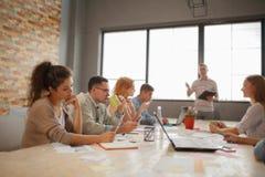 Gruppo di imprenditori attraenti nella riunione con le finestre luminose e la tavola di conferenza stipata di Immagine Stock