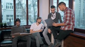 Gruppo di imprenditori che lavorano insieme e che prendono le note in un piccolo ufficio Riunione delle free lance, uomo con la b fotografie stock
