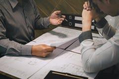Gruppo di ingegneria di costruzione o partner dell'architetto discutere un modello mentre controllando informazioni sul disegno e fotografie stock libere da diritti