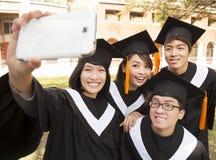 Gruppo di laureati che prendono immagine con il telefono cellulare Fotografie Stock