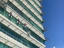 Gruppo di lavoratori che puliscono servizio di Windows su alta costruzione Fotografie Stock