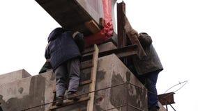 Gruppo di lavoratori maschii addetti all'azione nell'ambito di beem concreto sollevato enorme video d archivio