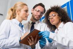 Gruppo di lavoratori scientifici che prendono le note che fanno ricerca in laboratorio, corsa Team Of Scientists Writing Results  Fotografia Stock Libera da Diritti