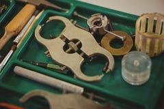 Gruppo di lavoro degli orologisti con l'orologio che ripara gli strumenti Fotografia Stock
